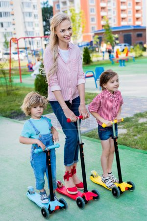 happy mother riding on kick scooters with adorable son and daughter at playground