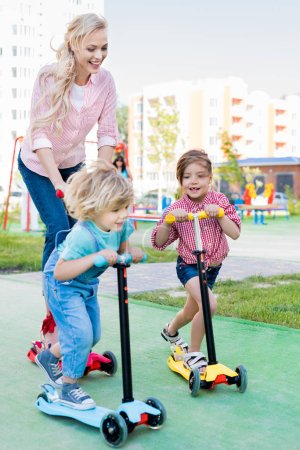 selective focus of mother riding on kick scooters with son and daughter at playground