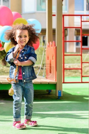 Photo for Smiling curly african american little child holding colorful balloons at playground - Royalty Free Image