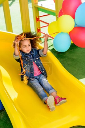 curly african american little child holding colorful balloons and sliding down from hill at playground