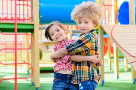 adorable little brother and sister embracing each other at playground