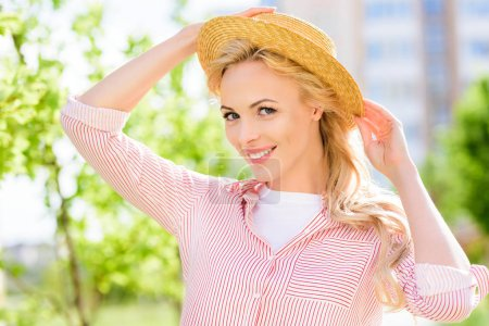 Photo for Portrait of smiling young woman in straw hat on blurred background - Royalty Free Image