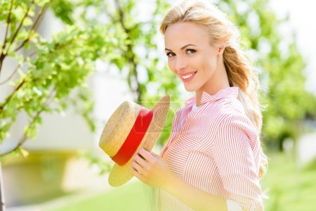 portrait of smiling young woman holding straw hat near trees