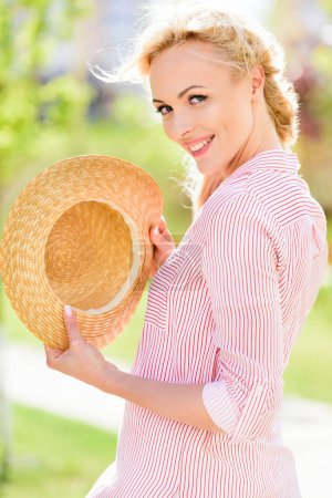 portrait of smiling young woman holding straw hat on blurred background