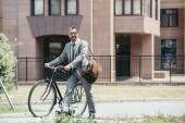 """Постер, картина, фотообои """"улыбающийся красивый бизнесмен, ходьба с велосипеда на улице в городе и глядя"""""""