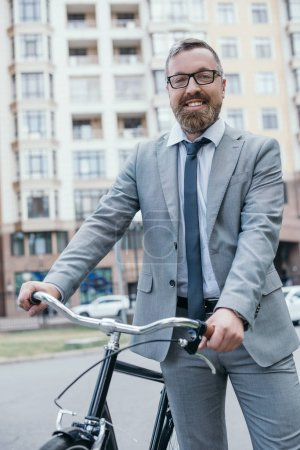 Photo for Happy handsome businessman in glasses standing with bicycle and looking at camera on street in city - Royalty Free Image
