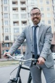 happy handsome businessman in glasses standing with bicycle and looking at camera on street in city