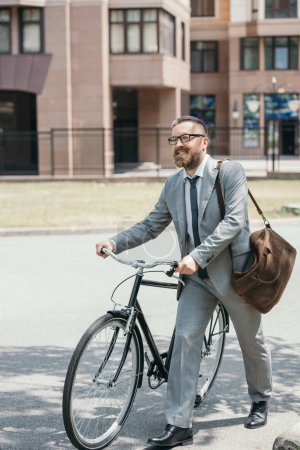 handsome businessman in grey suit and glasses walking with bike on street in city