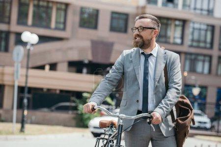 Photo pour Bel homme d'affaires marchant avec vélo sur rue dans la ville et à la recherche de suite - image libre de droit