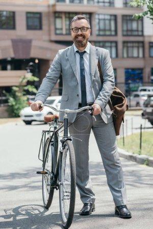 Photo pour Heureux homme d'affaires beau permanent avec vélo et regardant la caméra sur la rue dans la ville - image libre de droit