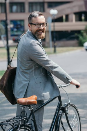 Photo for Smiling handsome businessman standing with bike and looking at camera on street in city - Royalty Free Image