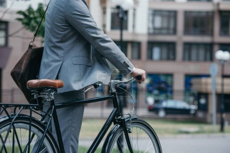 cropped image of businessman standing with bike on street in city