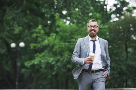 bearded smiling businessman walking on street and holding disposable coffee cup