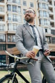 handsome bearded businessman with coffee and smartphone leaning on bicycle