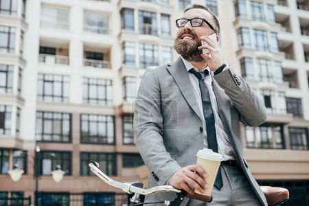 Photo for Bearded businessman with bicycle holding disposable cup of coffee and talking on smartphone - Royalty Free Image