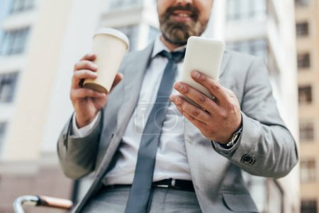 cropped view of businessman with coffee to go and smartphone