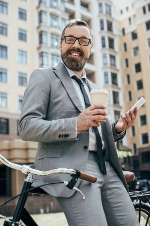 Photo for Bearded businessman with bicycle holding disposable cup of coffee and smartphone - Royalty Free Image