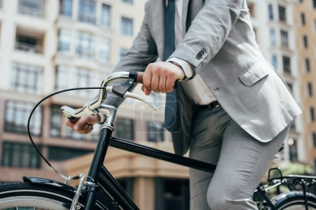 partial view of businessman in suit biking in city