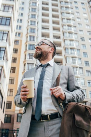 bottom view of businessman in suit with leather bag holding coffee to go