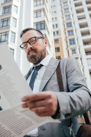 Photo for Bearded businessman reading newspaper in city - Royalty Free Image