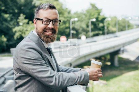 Photo pour Bel homme d'affaires détenant un gobelet jetable de café - image libre de droit
