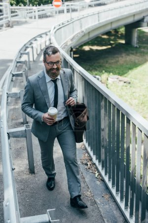 handsome businessman in formal wear with leather bag and coffee to go walking in city
