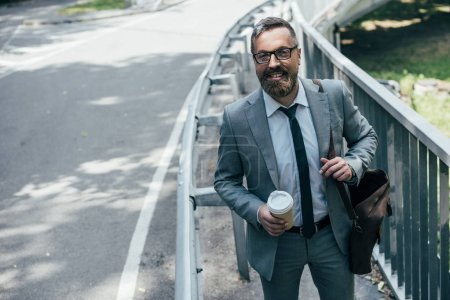 businessman in suit with leather bag and coffee to go walking in city