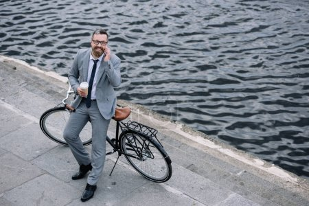 Photo pour Homme d'affaires avec café pour aller parler sur smartphone et permanent avec le vélo sur le quai - image libre de droit