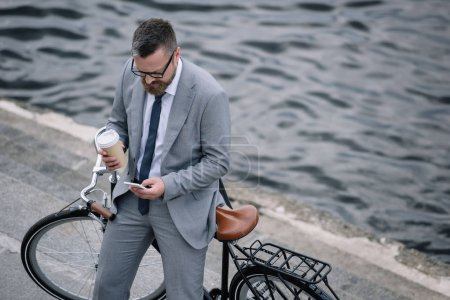 Photo for Businessman with coffee to go and smartphone standing with bike on quay - Royalty Free Image