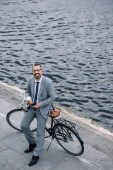 businessman with coffee to go and smartphone standing with bicycle on quay