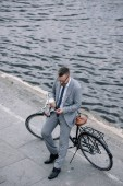 businessman with coffee to go using smartphone and standing with bike on quay