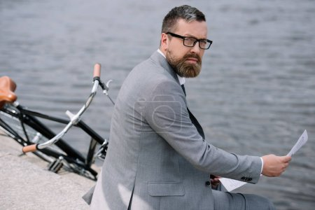 Photo for Bearded businessman with newspaper sitting on quay with bike - Royalty Free Image