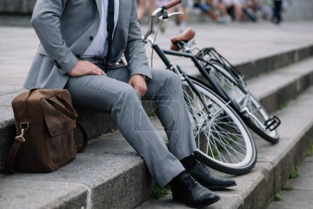 Photo for Cropped view of businessman in grey suit sitting on stairs with bike - Royalty Free Image