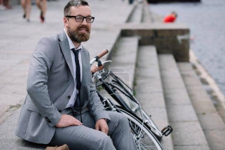 Photo pour Bel homme barbu en costume gris, assis dans les escaliers sur le quai avec vélo - image libre de droit