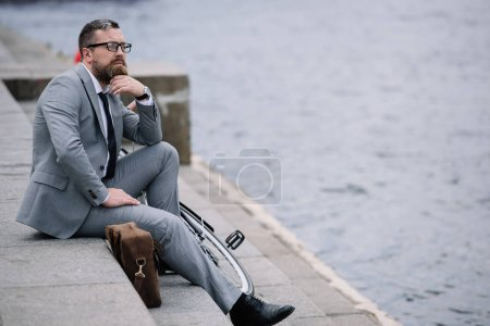 handsome thoughtful businessman in grey suit sitting on stairs on quay