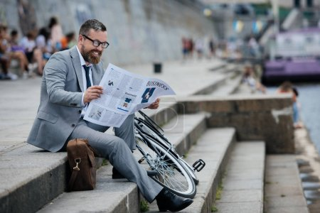 Photo for Businessman in grey suit reading newspaper on stairs with bicycle - Royalty Free Image