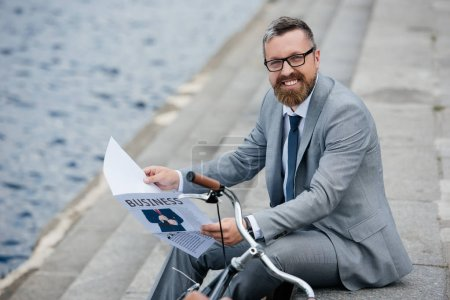 Photo for Handsome smiling businessman in grey suit reading newspaper on quay with bicycle - Royalty Free Image