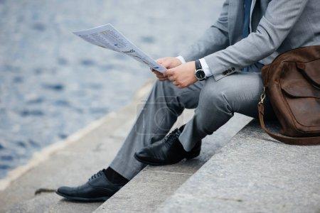 Photo pour Vue recadrée d'un homme d'affaires en costume gris lisant un journal sur quai - image libre de droit