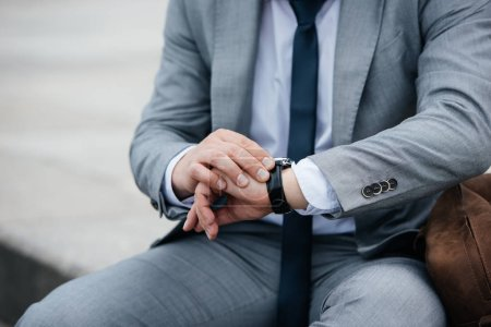 cropped view of businessman in grey suit looking at wristwatch