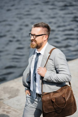 handsome bearded businessman in grey suit with leather bag walking on quay