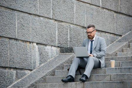 bearded businessman using laptop and sitting on stairs with coffee to go
