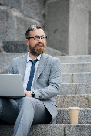 handsome businessman using laptop and sitting on stairs with disposable cup of coffee