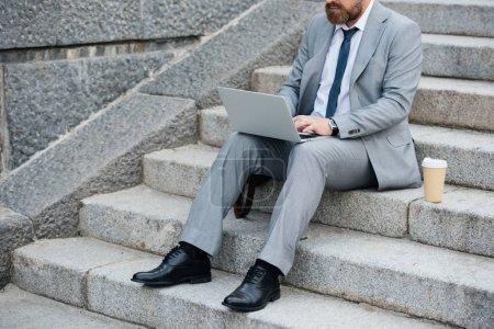 Photo pour Vue recadrée d'homme d'affaires avec gobelet jetable de café à l'aide d'ordinateur portable et assis dans les escaliers - image libre de droit