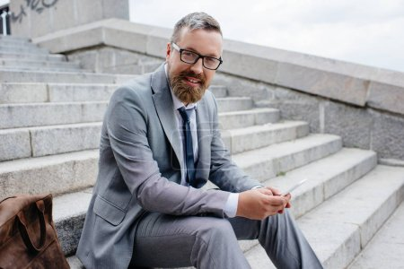 handsome businessman using smartphone and sitting on stairs in city