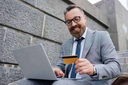smiling man shopping online with laptop and credit card
