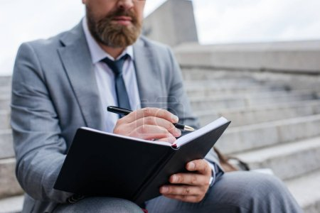 cropped view of businessman writing in diary and sitting on stairs