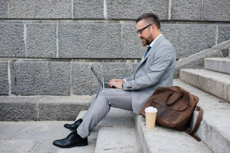 businessman with leather bag using laptop and sitting on stairs