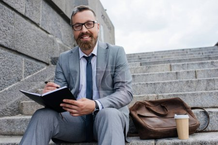 businessman with leather bag and coffee to go writing in diary and sitting on stairs