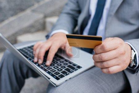 Photo pour Vue recadrée de l'homme faisant des achats en ligne avec ordinateur portable et carte de crédit - image libre de droit