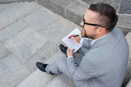 overhead view of businessman writing in planner